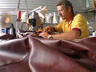 man stitching leather sofa
